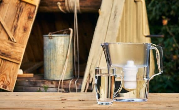 Water filter jug and a transparent glass cup of clean water in front of wooden draw well outdoors in summer evening at countryside