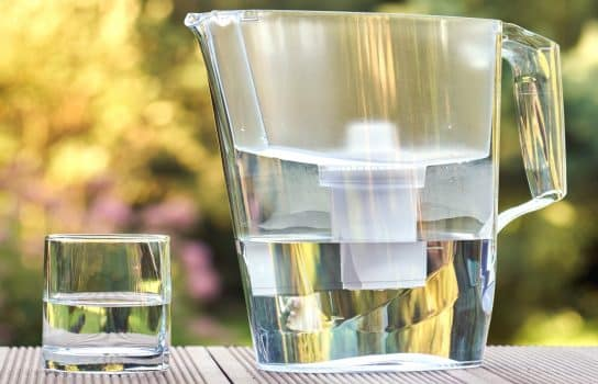 Plastic water filtration pitcher and a clean glass of a clear water on the summer garden background in sunny warm summer evening in countryside