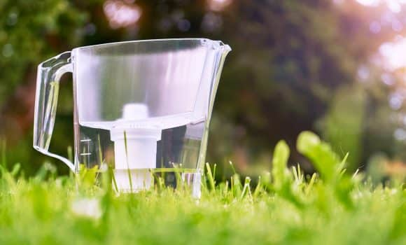 Water filter jug standing on the green grass in summer garden in warm morning. Water filtration concept.
