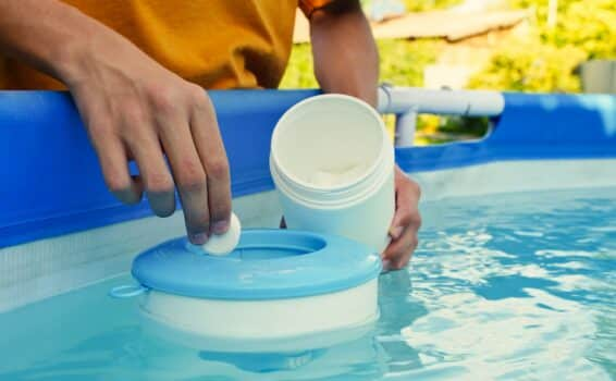 Hand holding white chlorine tablets over swimming pool skimmer. Chlorination of water in pool for disinfection and prevention against the development of microbes. High quality photo
