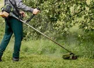 Worker with a gas mower in his hands, mowing grass in front of the house. Trimmer in the hands of a man. Gardener cutting the grass. Lifestyle