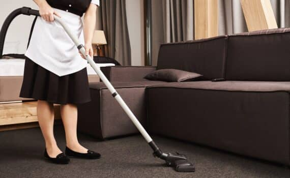 Clean house is key for productivity. Cropped shot of housemaid during work, cleaning living room with vacuum cleaner, removing dirt and mess near sofa. Maid is ready to make this place shine bright.