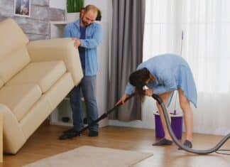 Man picking up sofa and wife cleans the dust under it with vacuum.