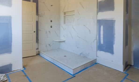 Renovation construction of master bathroom with new under construction bathroom interior drywall ready for tile in new luxury home