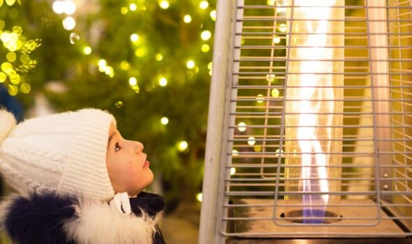 A little girl in a warm hat looks at the flame of a gas burner warming at a christmas market in the city. Lights of garlands in defocus on the christmas tree, new year, festive festivities