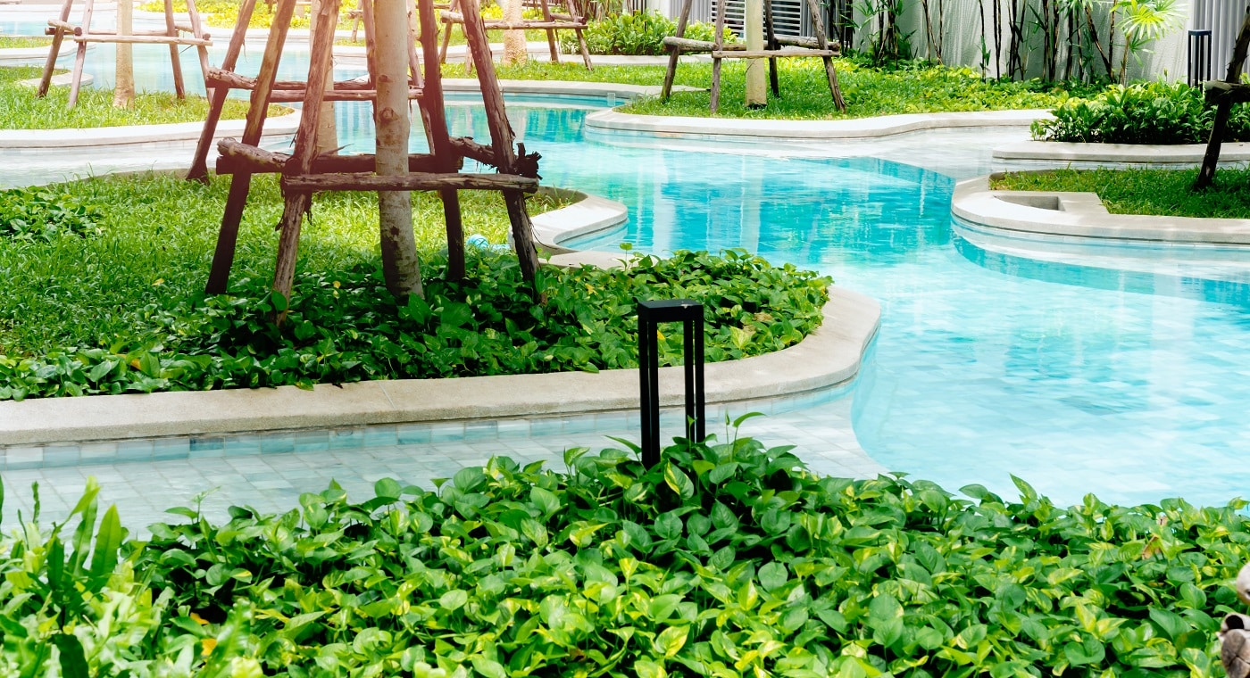 Pool with green gardens around. Garden and swimming pool decoration concept in hotel common area.