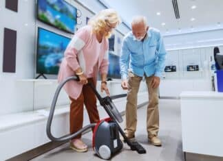 Cute smiling Caucasian senior couple trying out new vacuum cleaner for their home. Tech store interior.