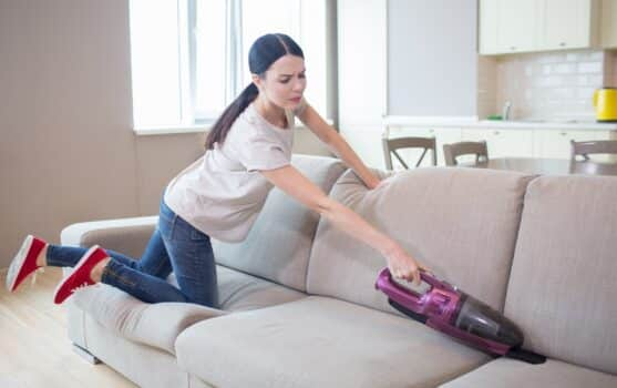 Hard-working woman stands on her knees on sofa and cleaning it with vacuum cleaner. She is trying to reach all parts of sofa