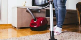 Young woman cleaning house with vacuum cleaner.