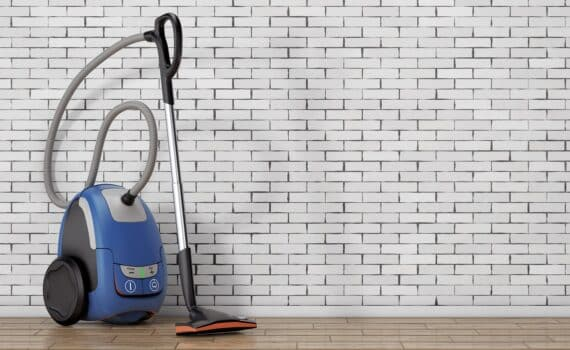Home appliance concept. Modern vacuum cleaner in front of brick wall. 3d rendering.