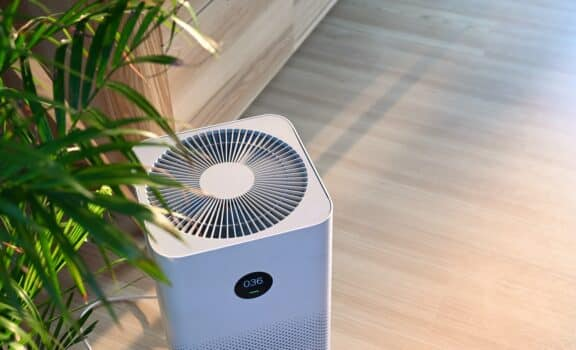 Air purifier on wooden floor in comfortable home. Fresh air and healthy life.