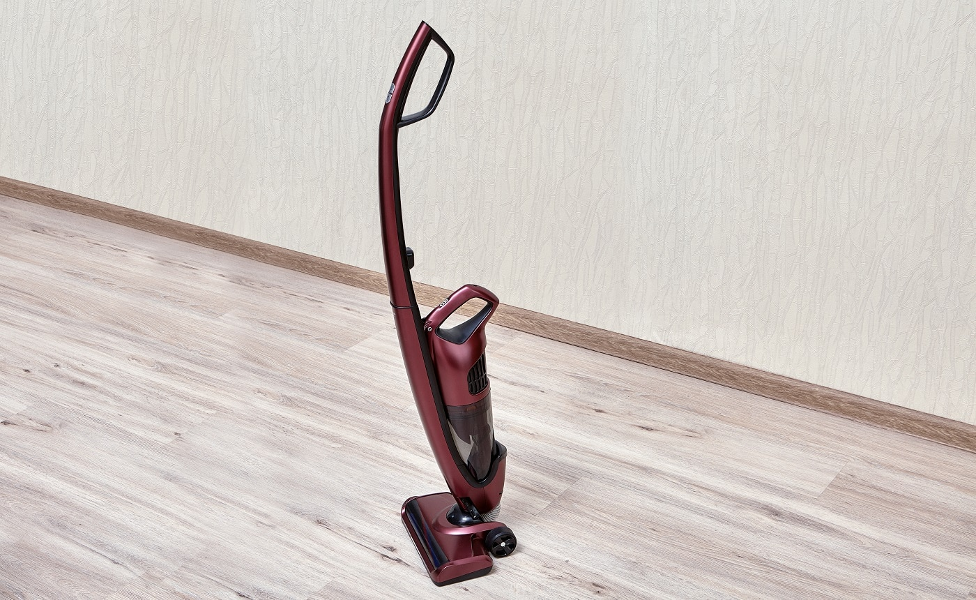 Handheld vacuum cleaner with a separate small dust tank in an empty room.