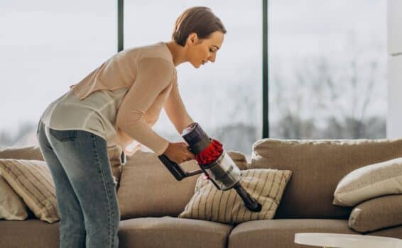 Young woman with rechargeable vacuum cleaner cleaning at home