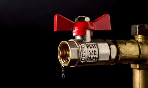 Ball valves close-up on a black background from which water is dripping. Plumbing renovation concept