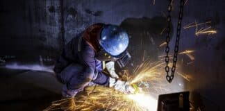 Male worker grinding on steel plate with flash of sparks close up wear protective gloves oil inside confined spaces.