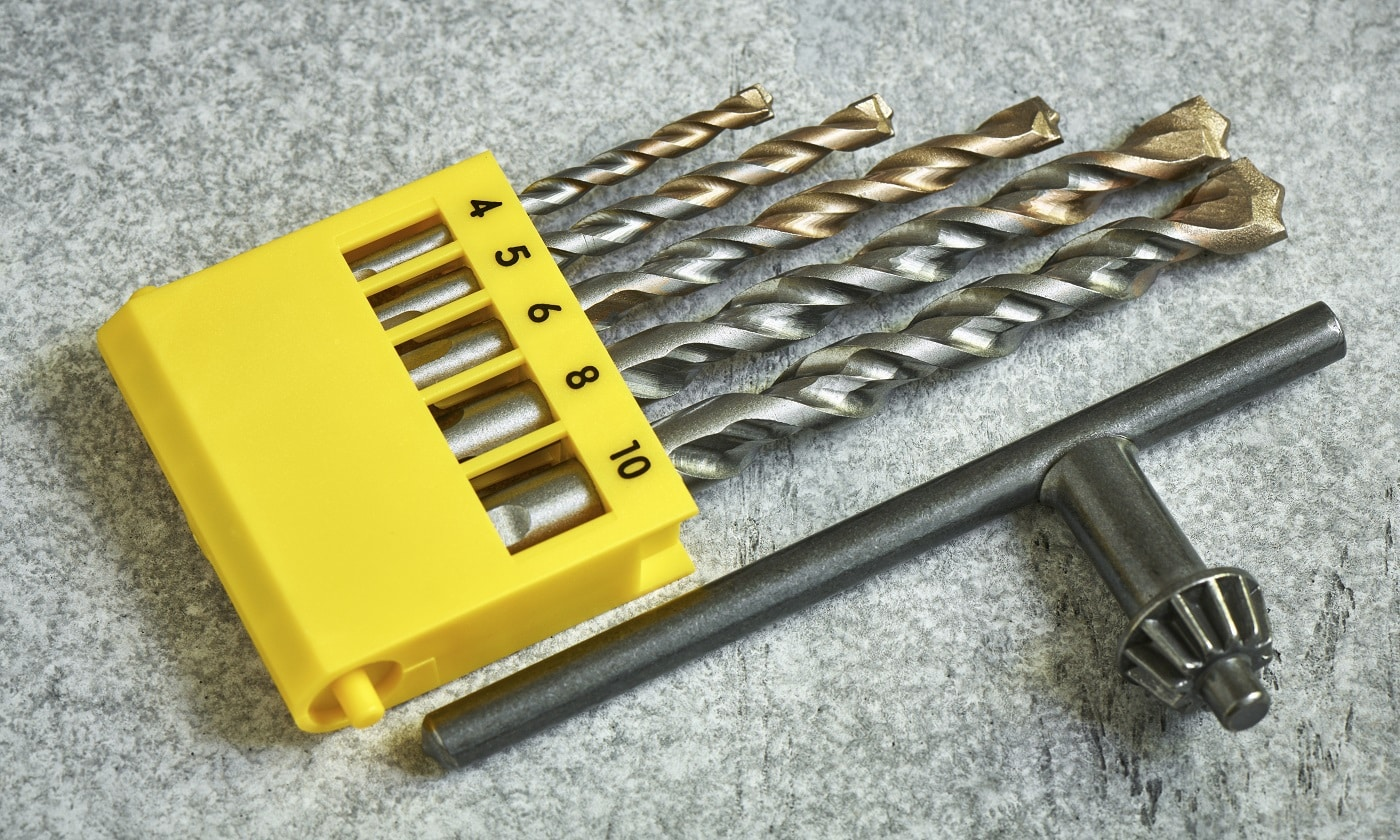 Set of various diameters of winning drills and a drill chuck wrench, close up, shallow depth of sharpness