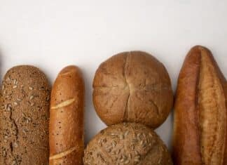 top view of different types of bread as baguette cob rye on white background with copy space