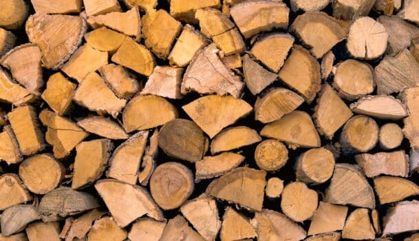 Material for heating the house. Preparation of firewood for the winter. Background of firewood. A pile of firewood.