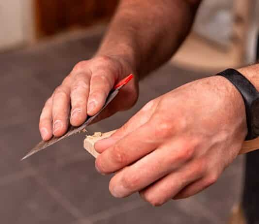 Close-up A male carpenter in work clothes restoring a wooden bar with wax and a spatula on a wooden table